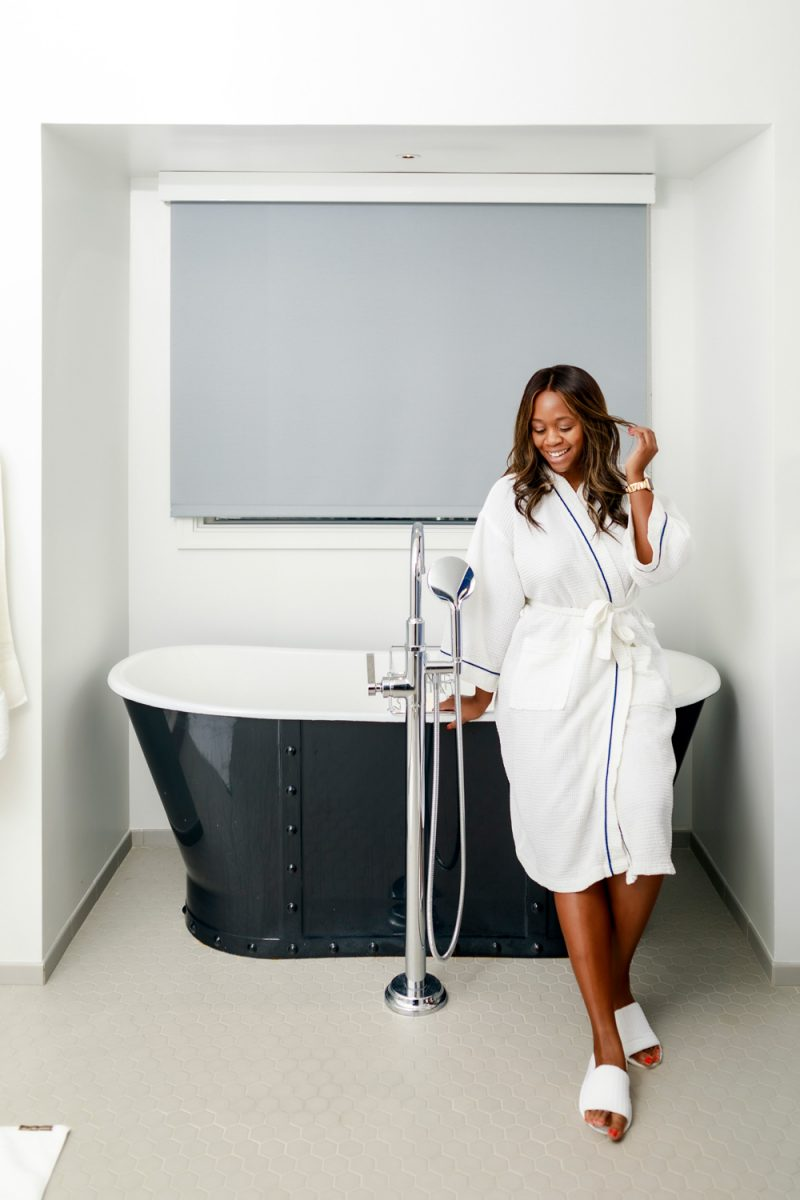The Tides Inn Ashburn Suite | Tides Inn in Irvington by popular D.C. travel blogger, Alicia Tenise: image of Alicia Tenise wearing a white robe and leaning against a black soaking tub.