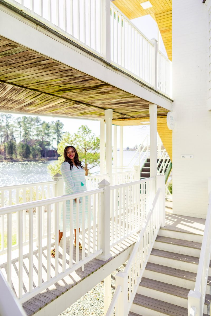 The Tides Inn, Sail to Sable x Style Charades Anne Printed Dress |Tides Inn in Irvington by popular D.C. travel blogger, Alicia Tenise: image of Alicia Tenise waring a blue and white stripe dress and standing on a balcony.