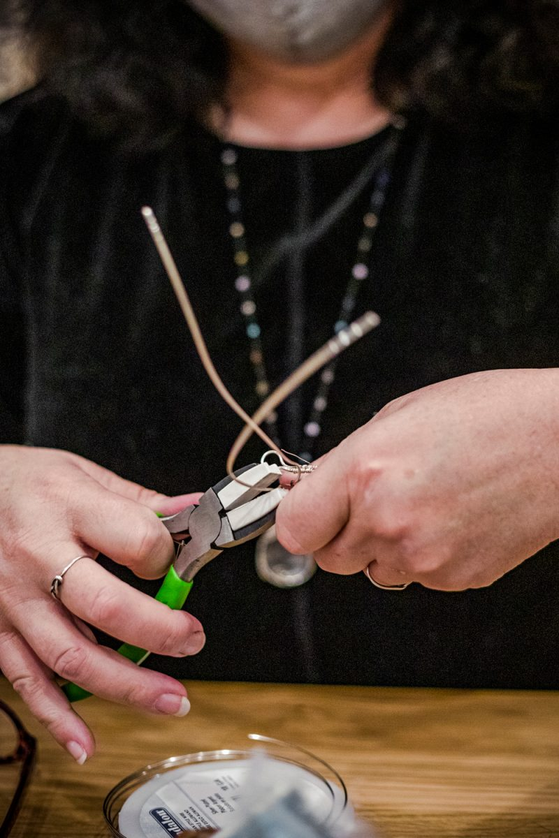 Oyster Jewelry Making Class at the Tides Inn |Tides Inn in Irvington by popular D.C. travel blogger, Alicia Tenise: image of a woman using some wire cutters to cut some wire.