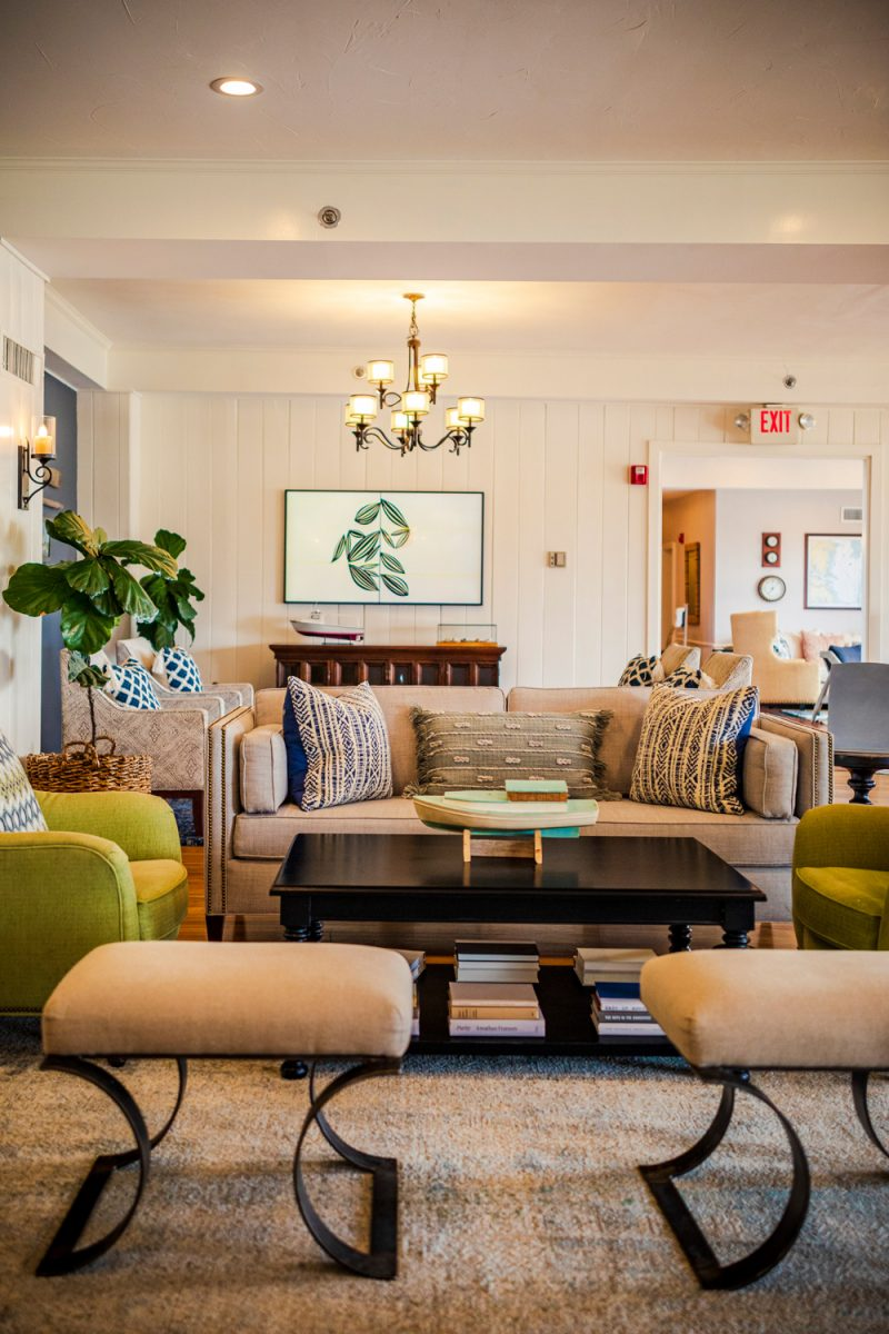 Tides Inn in Irvington by popular D.C. travel blogger, Alicia Tenise: image of a sitting area decorated with a cream couch and green armchairs.