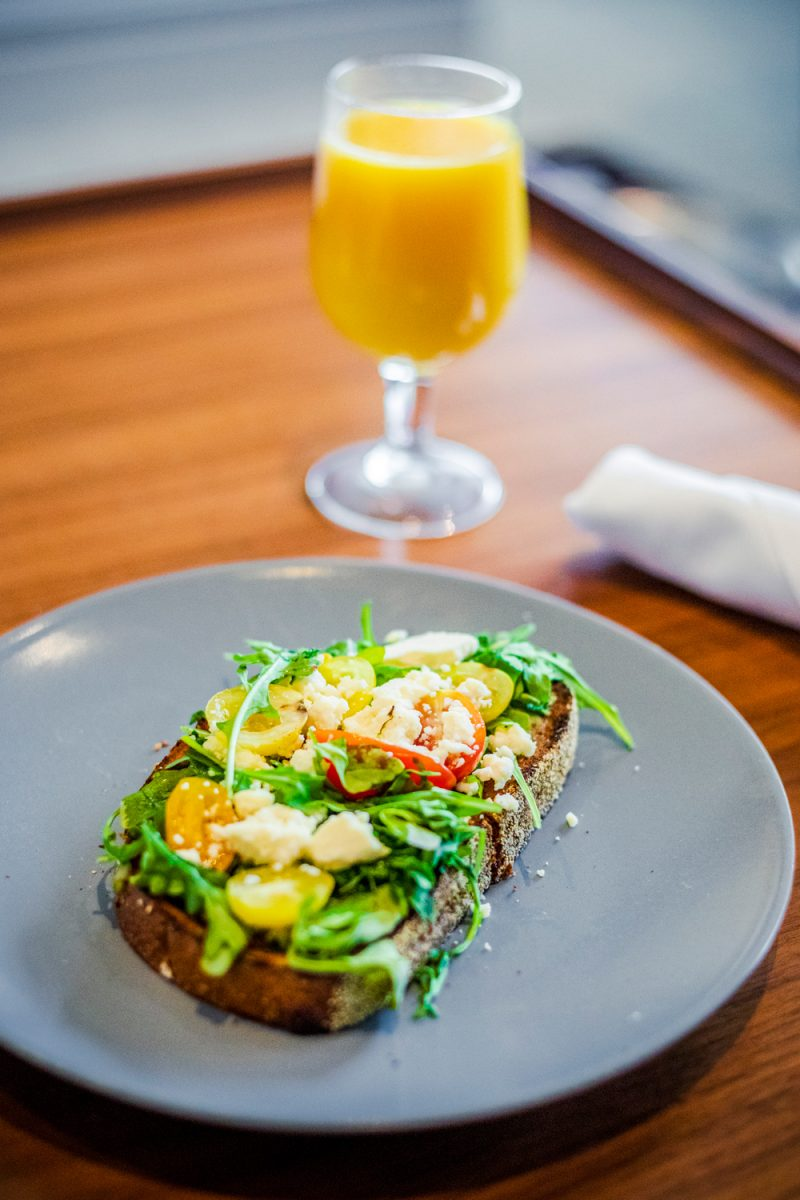 Avocado Toast at the Tides Inn, In-Room Dining from the Chesapeake Restaurant & Terrace |Tides Inn in Irvington by popular D.C. travel blogger, Alicia Tenise: image of avocado toast next to a glass of orange juice.