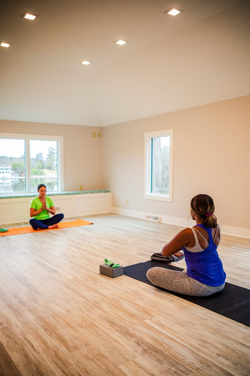 Yoga Class at the Tides Inn |Tides Inn in Irvington by popular D.C. travel blogger, Alicia Tenise: image of Alicia Tenise sitting on a yoga mat in front of a Yoga Instructor.