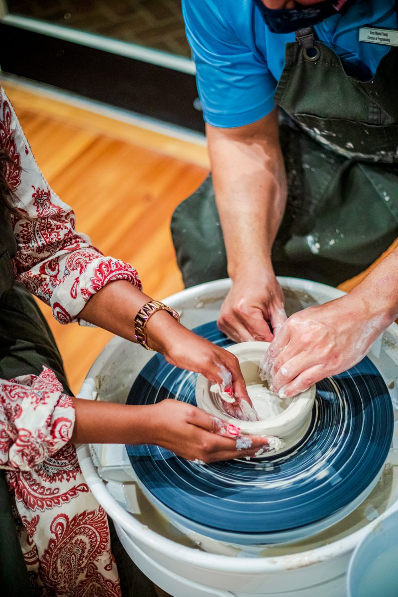 The Tides Inn Pinot and Pottery Class |Tides Inn in Irvington by popular D.C. travel blogger, Alicia Tenise: image of two people making pottery on a pottery wheel.