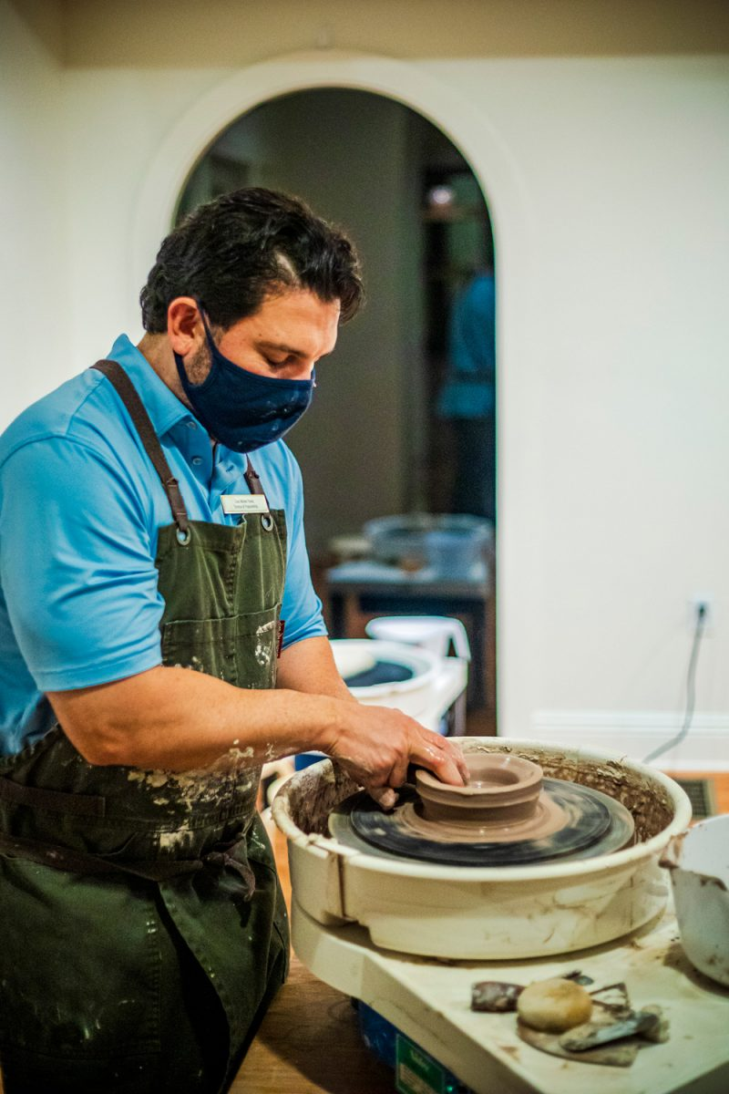 Pottery and Pinot Class at the Tides Inn |Tides Inn in Irvington by popular D.C. travel blogger, Alicia Tenise: image of a man molding some clay on a pottery wheel.