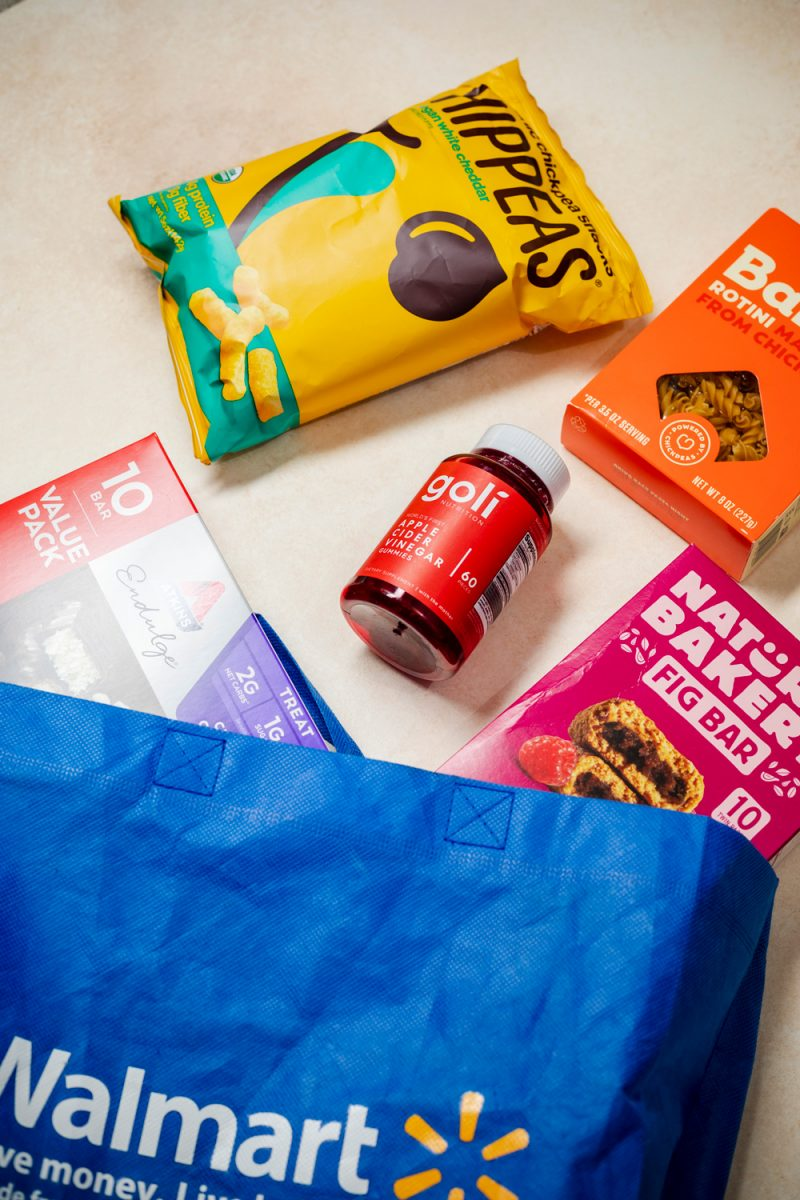 Walmart+ Free Delivery |Walmart Wellness Hub by popular D.C. lifestyle blogger, Alicia Tenise: image of Hippeas, Goli gummies, Banza pasta, Nature's Bakery fig bar, Atkin's bars value pack and a reusable Walmart shopping bag.