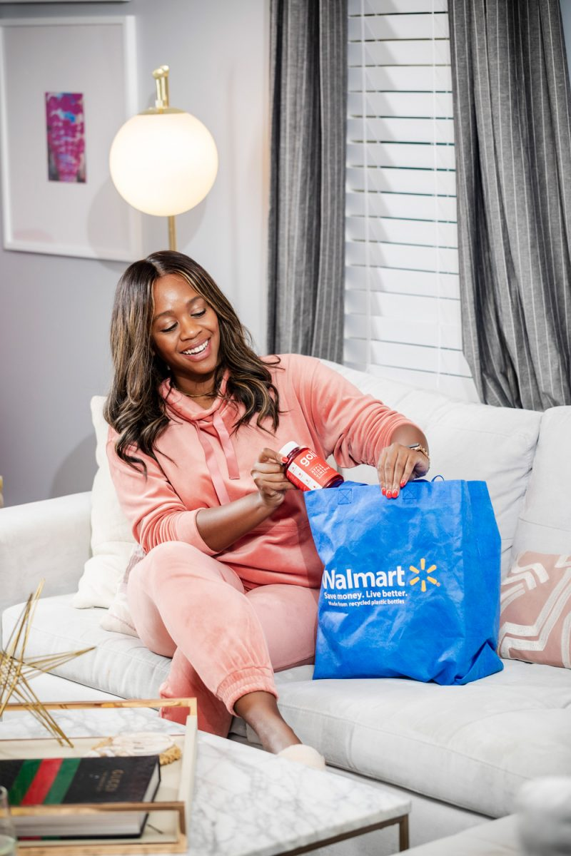 Walmart Wellness Hub, Walmart Scoop Women's Funnel Neck Velour Sweatshirt with Pockets, Walmart Scoop Women's Velour Joggers |Walmart Wellness Hub by popular D.C. lifestyle blogger, Alicia Tenise: image of Alicia Tenise sitting on her couch and wearing a pink Velour jogging suit while pulling items out of a reusable Walmart shopping bag.