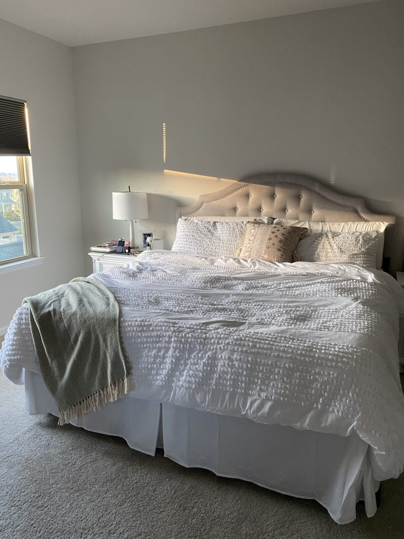 Master Bedroom Design Ideas by popular D.C. life and style blogger, Alicia Tenise: image of a master bedroom with a bed that has a grey tuft headboard and white and grey bedding.