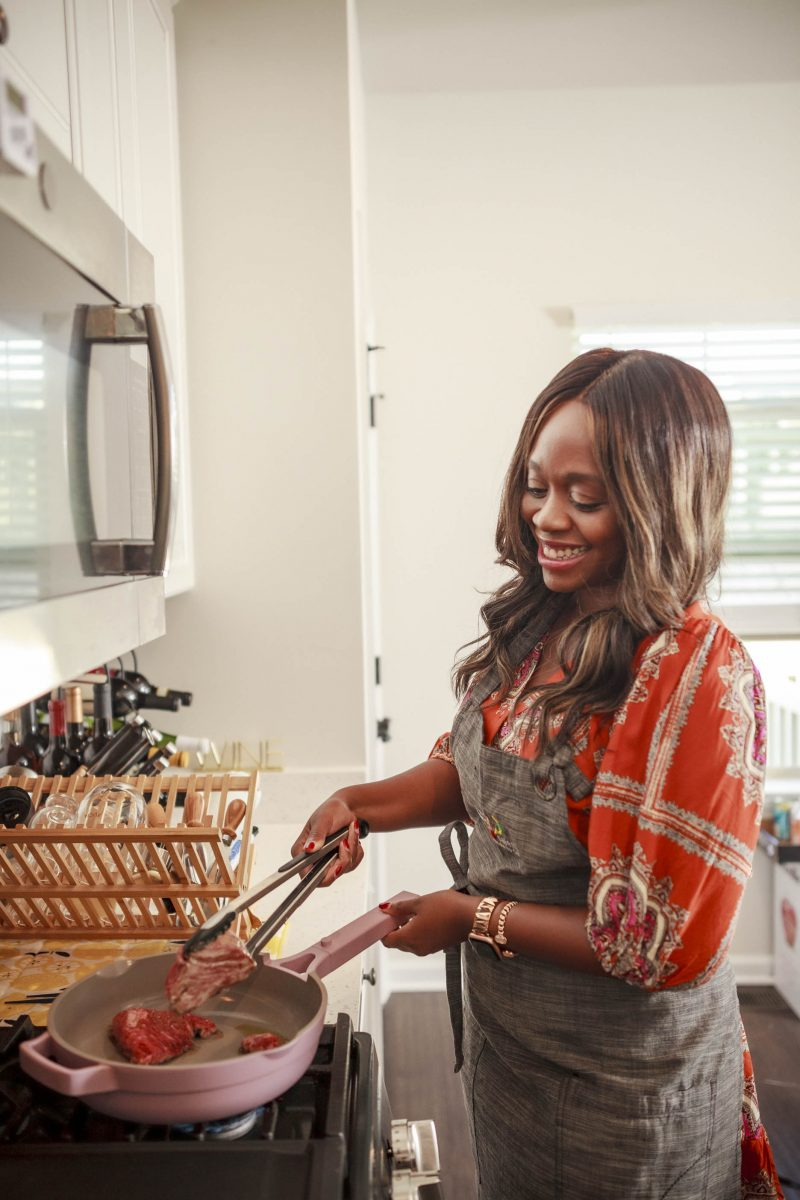 Valentine's Day Dinner by popular D.C. lifestyle blogger, Alicia Tenise: image of Alicia Tenise wearing a grey apron and cooking in a pink Always Pan.