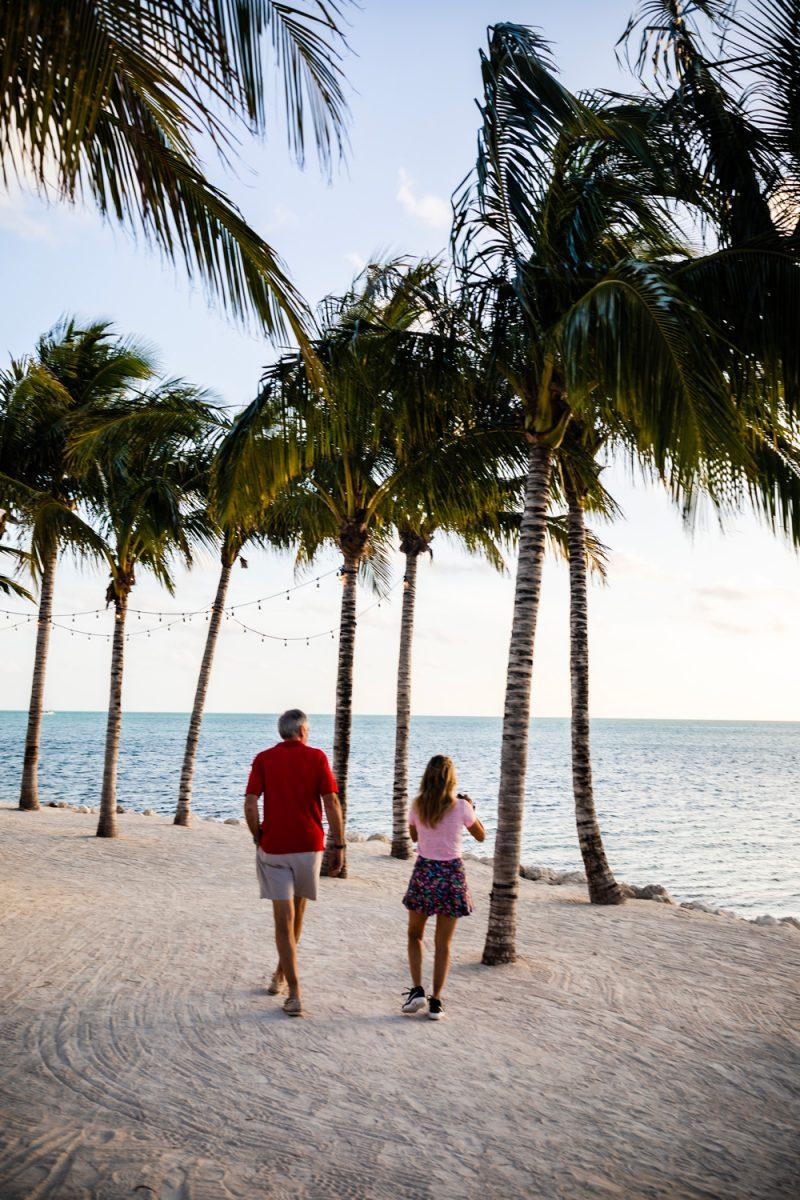 Isla Bella Resort Marathon Florida | Florida Keys Road Trip by popular D.C. travel blogger, Alicia Tenise: image of a couple walking on a white sand beach under some palm trees at Isla Bella Resort in Marathon Florida.