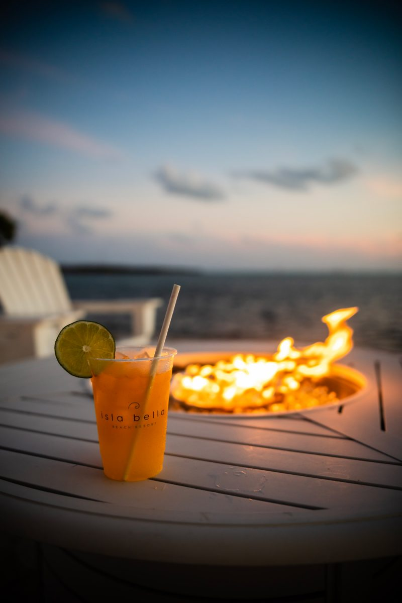 Isla Bella Resort Marathon Florida |Florida Keys Road Trip by popular D.C. travel blogger, Alicia Tenise: image of a alcoholic drink in an Isla Bella cup next to a fire pit.