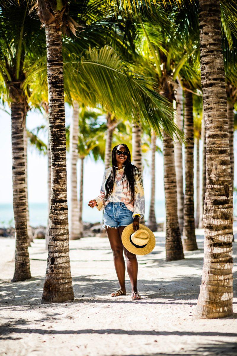 Isla Bella Resort Marathon Florida |Florida Keys Road Trip by popular D.C. travel blogger, Alicia Tenise: image of Alicia Tenise walking under some palm trees at the Isla Bella beach resort.