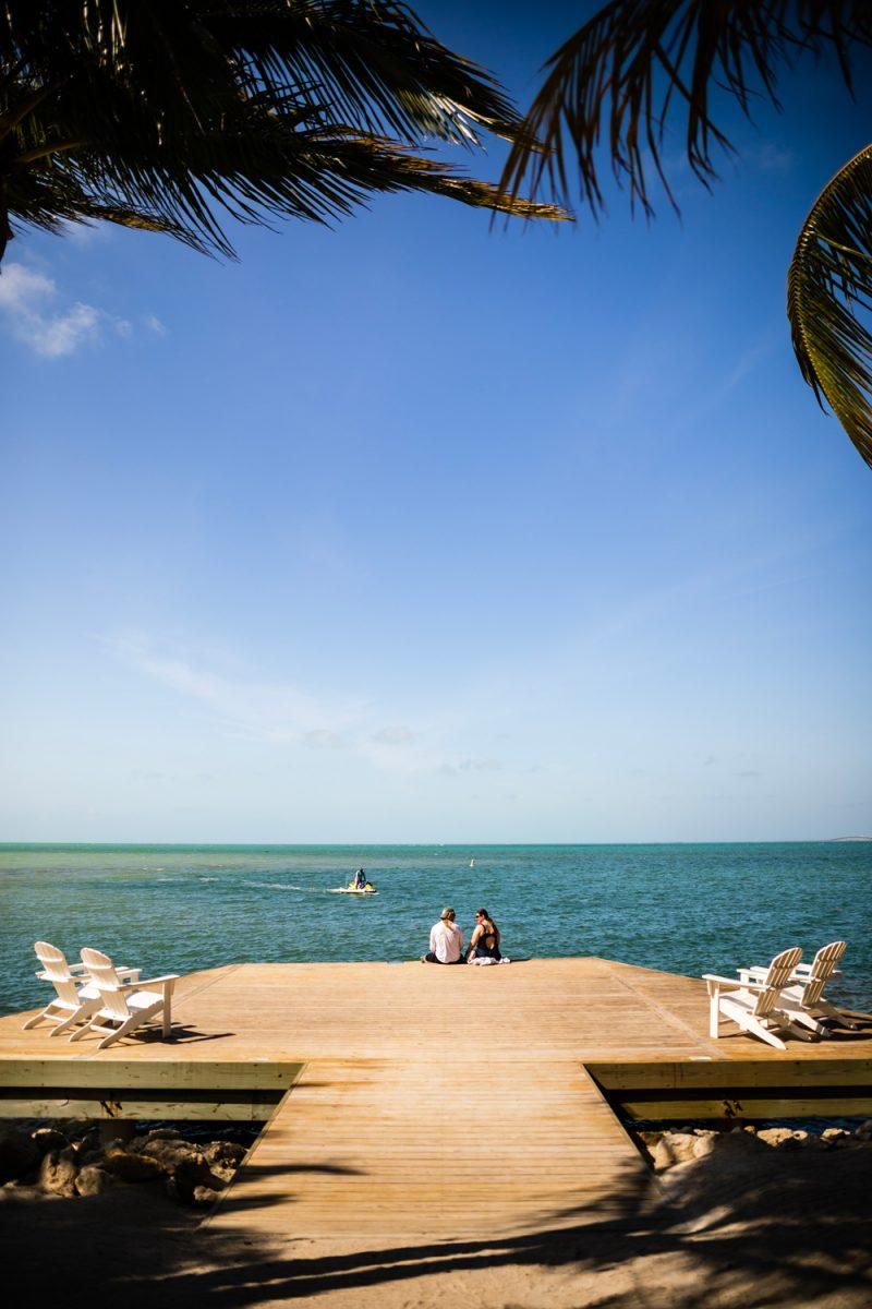 Isla Bella Beach Resort |Florida Keys Road Trip by popular D.C. travel blogger, Alicia Tenise: image of two women sitting on a dock at the Isla Bella Beach resort.