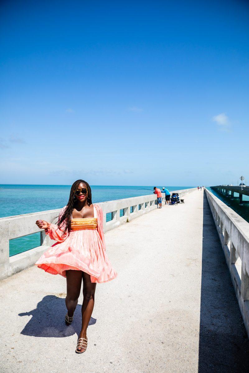 Seven Mile Bridge Florida Keys |Florida Keys Road Trip by popular D.C. travel blogger, Alicia Tenise: image of Alicia Tenise walking on Seven Mile Bridge.
