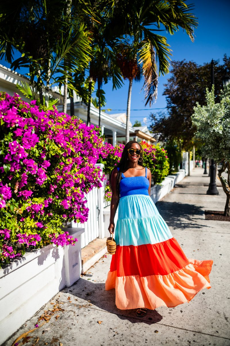 Key West Travel Ideas |Florida Keys Road Trip by popular D.C. travel blogger, Alicia Tenise: image of Alicia Tensie standing next to a pink flowering bush in the Florida Keys and wearing a multi color maxi dress.