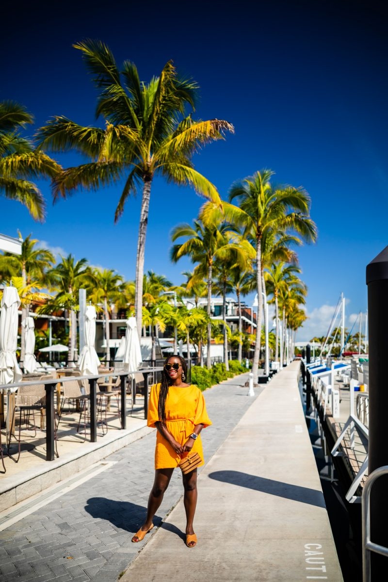 The Perry Hotel Key West |Florida Keys Road Trip by popular D.C. travel blogger, Alicia Tenise: image of Alicia Tenise wearing a yellow jumpsuit and standing outside the Perry Hotel.