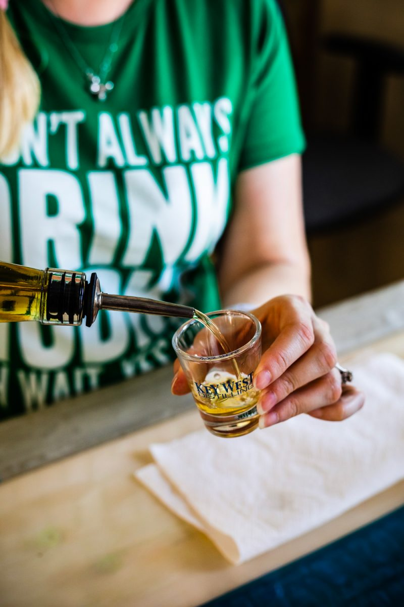 Key West Distilling |Florida Keys Road Trip by popular D.C. travel blogger, Alicia Tenise: image of a woman pouring some alcohol into a Key West distillery shot glass.