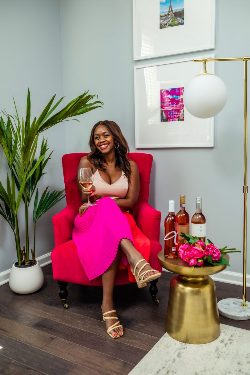 Cushnie for Target Dress | Black Owned Businesses by popular D.C. lifestyle blogger, Alicia Tenise: image of Alicia Tenise sitting in a red velvet chair and wearing a Cushnie for Target pink and red dress and holding a glass of rose wine.