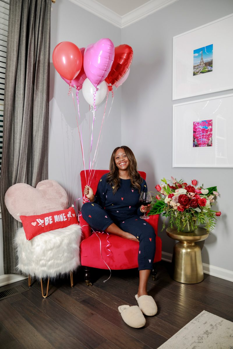 Lou & Grey Colorful Heart Terry Sweatshirt, Lou & Grey Colorful Heart Terry Sweatpants |Valentine's Day Outfit by popular D.C. fashion blogger, Alicia Tenise: image of Alicia Tenise sitting on a red chair and holding a bunch of heart shaped balloons and wearing a heart print loungewear set and pair of fuzzy slippers.