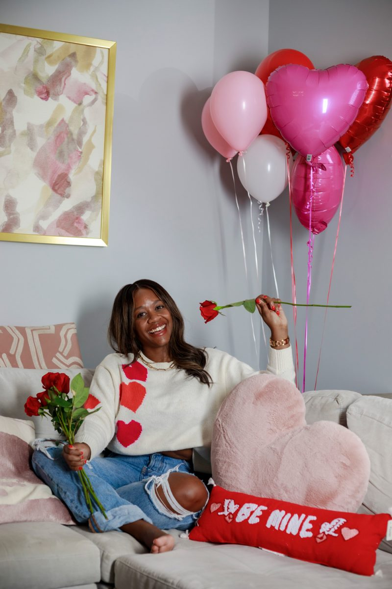 Lou & Grey Heart Sweater, Casual Valentine's Day Outfit Ideas | Valentine's Day Outfit by popular D.C. fashion blogger, Alicia Tenise: image of Alicia Tenise sitting on her couch that's decorated with Valentine's throw pillow and holding a bunch of roses while wearing a heart print sweater and distressed jeans.