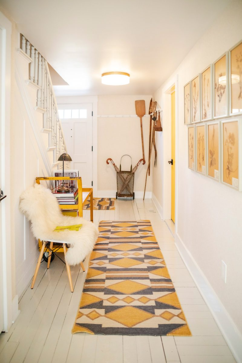 White Moose Inn Washington VA |Washington VA by popular D.C. travel blogger, Alicia Tenise: image of a hallway with a yellow and grey geometric runner rug, sheepskin chair, yellow prints in white frames and a white wood floor.