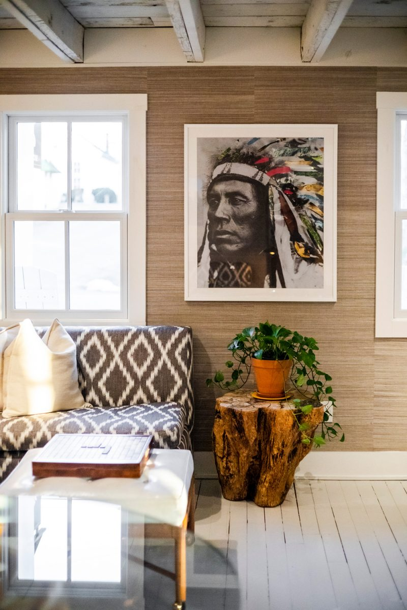 White Moose Inn Washington VA |Washington VA by popular D.C. travel blogger, Alicia Tenise: image of a room decorated with a Native American print, white wood floor, wooden stump end table, white ottoman, and geometric couch.