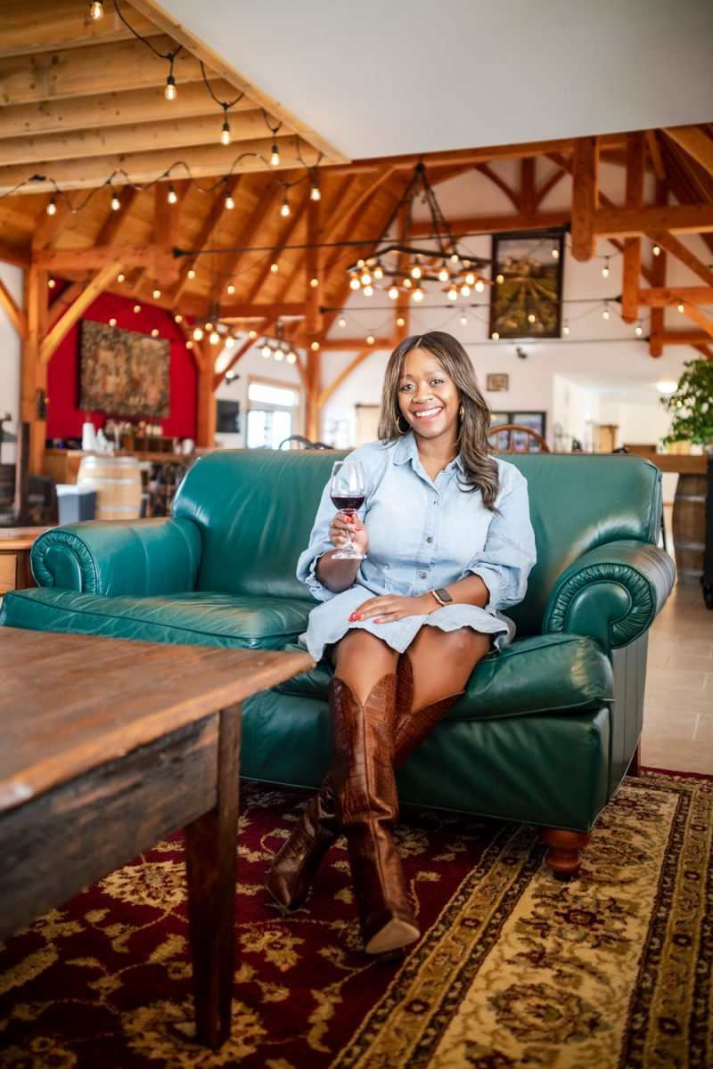 quievremont winery |Washington VA by popular D.C. travel blogger, Alicia Tenise: image of Alicia Tenise sitting on a green leather couch and wearing a denim dress and brown knee high cowboy boots while holding a glass of red wine.