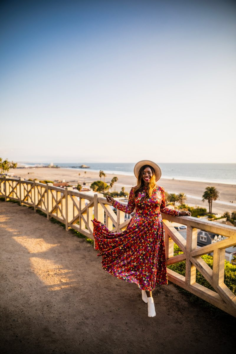 Santa Monica | Moving Cross Country by popular LA lifestyle blogger, Alicia Tenise: image of Alicia Tenise wearing a floral print maxi dress, white ankle boots, and straw hat while standing outside on a walking path near the ocean in Santa Monica, California.