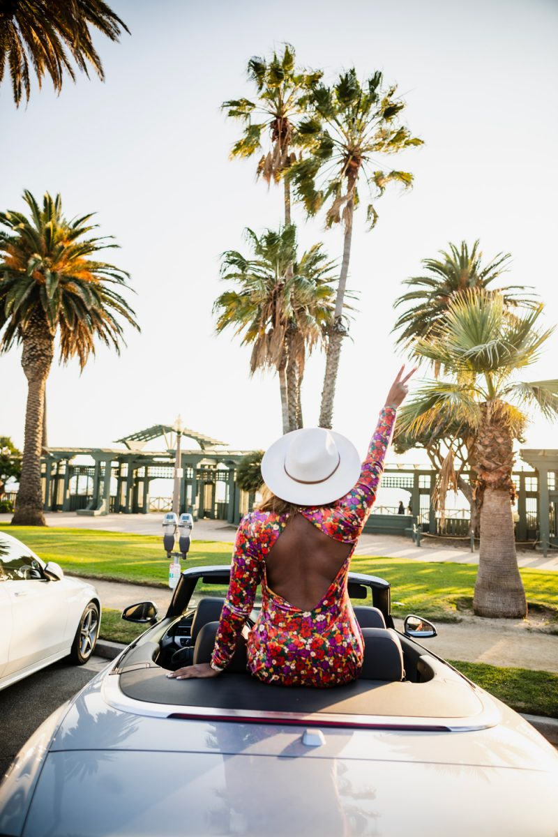 Santa Monica California, | Life Update by popular D.C. lifestyle blogger, Alicia Tenise: image of a woman sitting in a convertible car parked in front of some palm trees and wearing floral print dress and white fedora hat.
