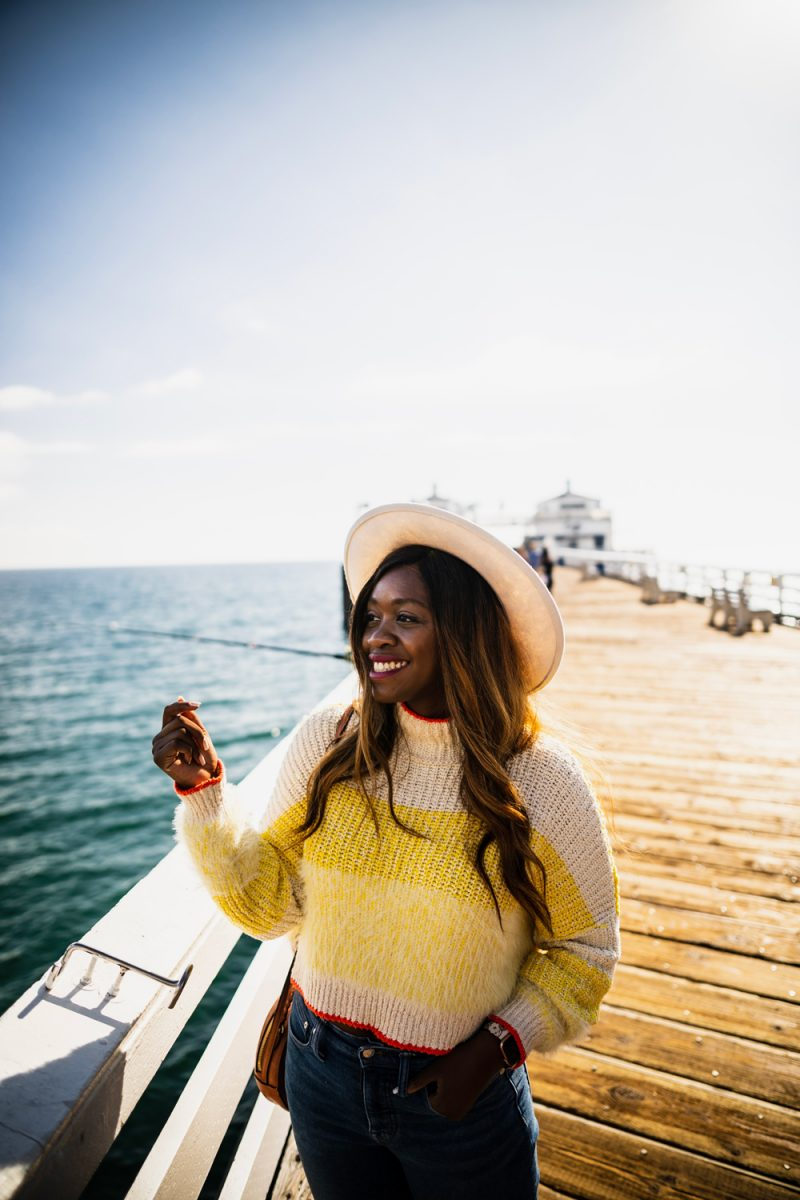 Life Update by popular D.C. lifestyle blogger, Alicia Tenise: image of Alicia Tenise, standing on Malibu Pier and wearing a yellow and cream stripe sweater, white fedora hat, and jeans.