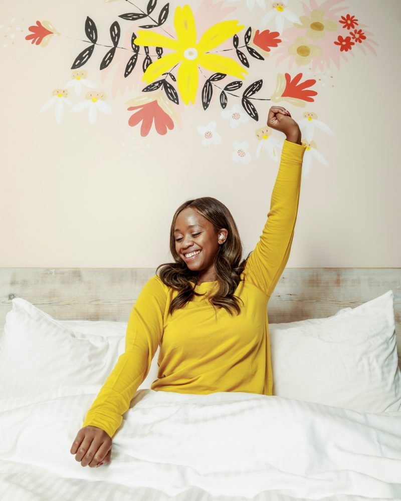 Lou and Grey Signaturesoft Sweatshirt, Quirk Hotel Richmond Virginia | Bose Sleepbuds 2 by popular D.C. lifestyle blogger, Alicia Tenise: image of Alicia Tenise wearing a yellow long sleeve top and sitting in a bed with white bedding while wearing a pair of Bose Sleepbuds 2.