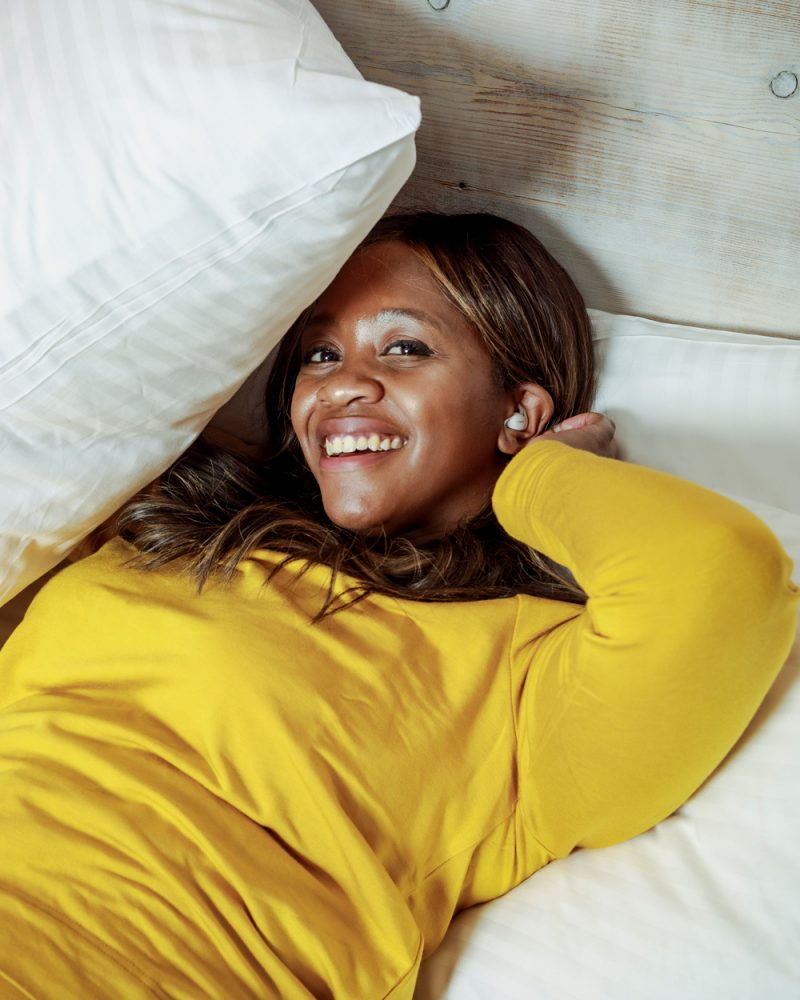 Bose Sleepbuds 2 by popular D.C. lifestyle blogger, Alicia Tenise: image of Alicia Tenise wearing a yellow long sleeve top and laying in a bed with white bedding while wearing a pair of Bose Sleepbuds 2.