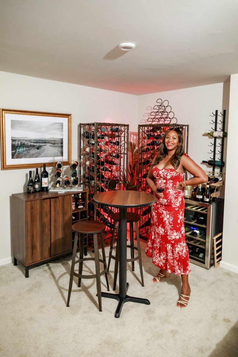 At Home Wine Cellar ideas featured by top VA lifestyle blogger, Alicia Tenise | Lowe's Home Wine Cellar by popular D.C. lifestyle blogger, Alicia Tenise: image of Alicia Tenise wearing a red and white floral maxi dress and standing in a wine cellar with a Lowe's Steel Metal Wine Rack, Lowe's Wine Cabinet, Lowe's 29-Bottle Wine Chiller, Lowe's Round Bar Table, Lowe's Bar Stools, Lowe's LED Light Strips, Lowe's Wall-Mounted Wine Rack, Lowe's Wood Wine Rack, and Lowe's Gold Metal Rectangular Wine Rack.