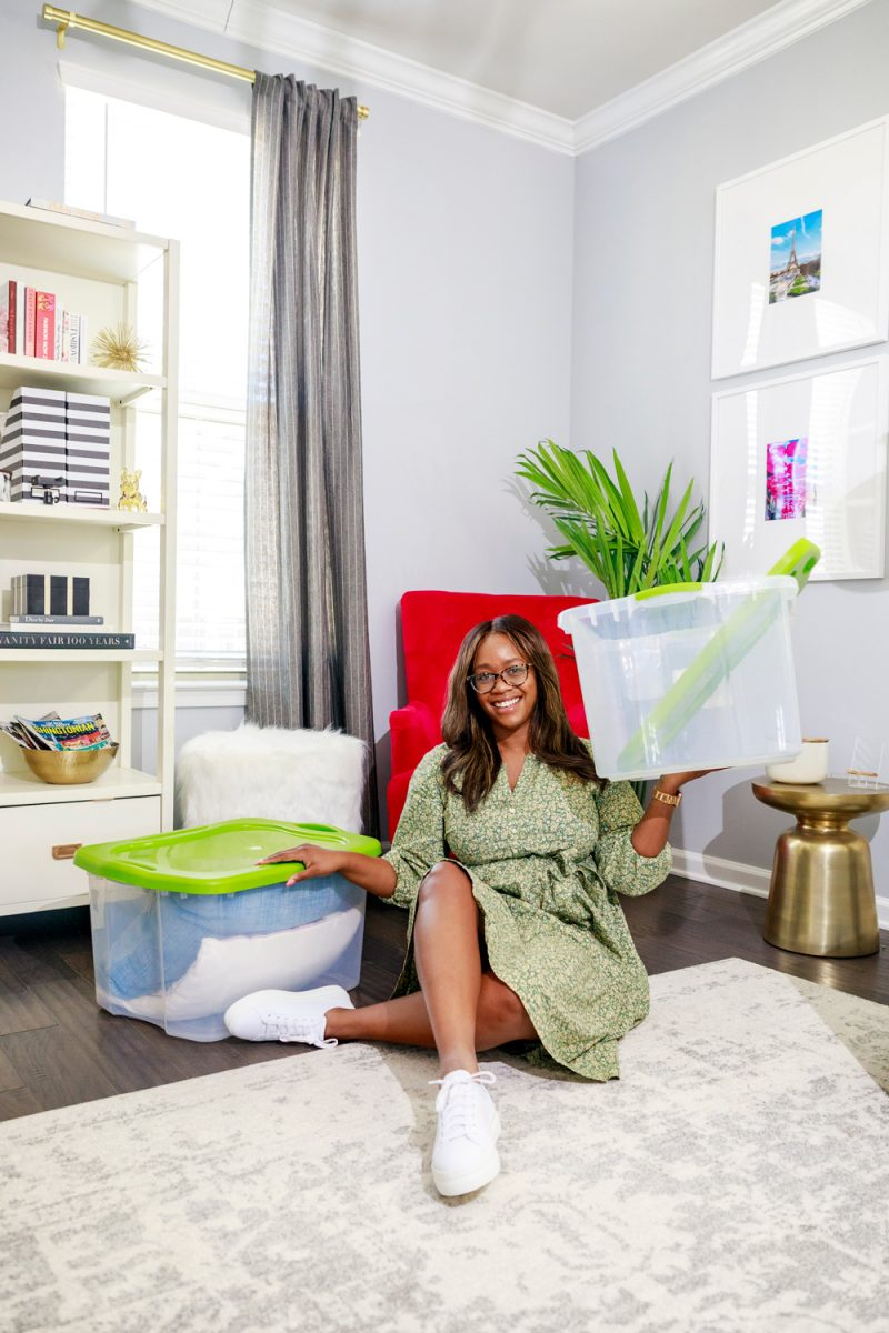 Spring Cleaning Tips and Tricks by popular D.C. life and style blogger, Alicia Tenise: image of Alicia Tenise sitting on the floor next to some clear storage bins with green lids.