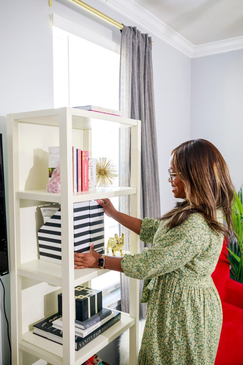 Spring Cleaning Tips and Tricks by popular D.C. life and style blogger, Alicia Tenise: image of Alicia Tenise putting black and white stripe magazine holders on a white shelf.