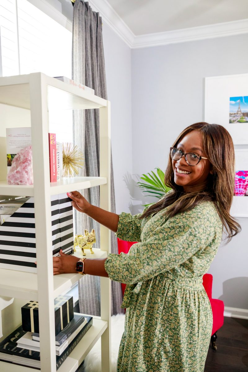 Spring Cleaning Tips and Tricks by popular D.C. life and style blogger, Alicia Tenise: image of Alicia Tenise place black and white stripe magazine holders on a white shelving unit.