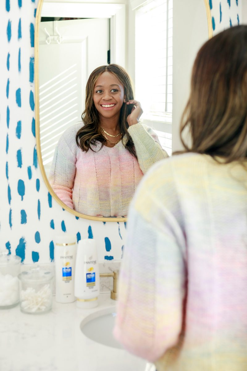 Sephora Spring Skincare Essentials | Sephora Skincare by popular D.C. beauty blogger, Alicia Tenise: image of Alicia Tenise wearing a pastel rainbow sweater and looking at herself in her bathroom mirror.