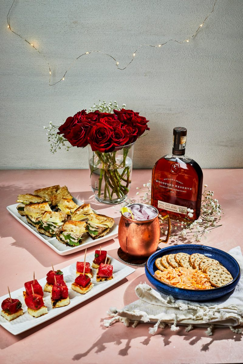 Kentucky Derby Party essentials featured by top US lifestyle blogger, Alicia Tenise - Woodford Spire Cocktail, Smoked Turkey & Brie with Apple ButterOlive Oil and Pepper-Marinated Watermelon Bites with Halloumi, Pimento Cheese, |Kentucky Derby Party by popular D.C. lifestyle blogger, Alicia Tenise: image of a bottle of whiskey, vase of red roses, whiskey cocktail in a copper mug, crackers and pimento cheese, watermelon bites, and sandwiches with turkey and smoked brie.