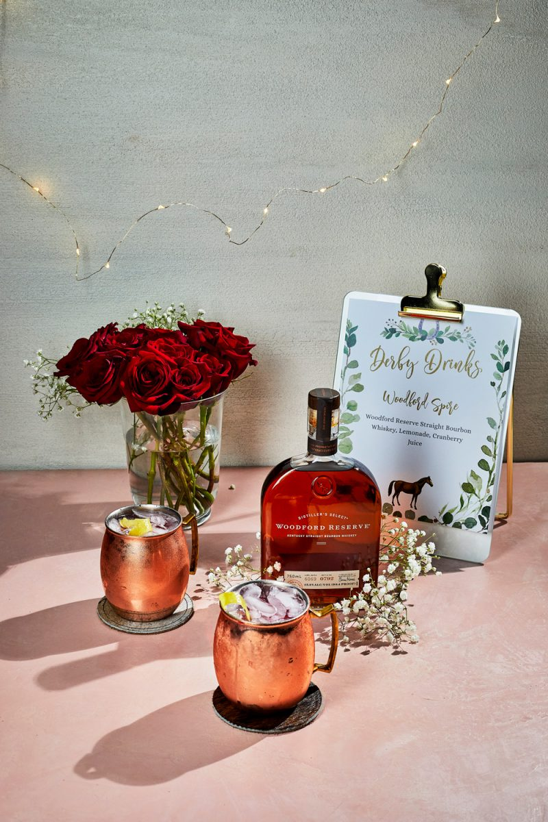 Kentucky Derby Party essentials featured by top US lifestyle blogger, Alicia Tenise: The Woodford Spire Cocktail |Kentucky Derby Party by popular D.C. lifestyle blogger, Alicia Tenise: image of two whiskey cocktails in copper mugs next to a bottle of whiskey and a vase of red roses.