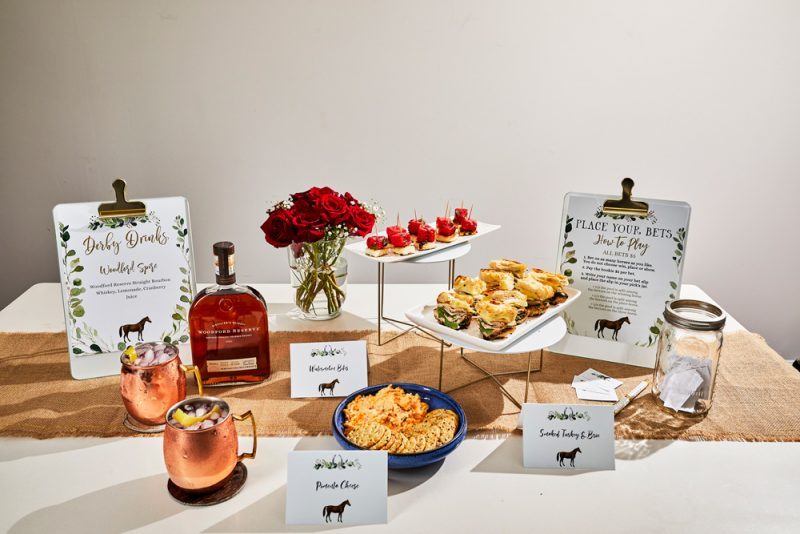 Kentucky Derby Party essentials featured by top US lifestyle blogger, Alicia Tenise | Kentucky Derby Party by popular D.C. lifestyle blogger, Alicia Tenise: image of appetizers and drinks in copper mugs next to horse food labels, a vase of red roses, and a bottle of whiskey.