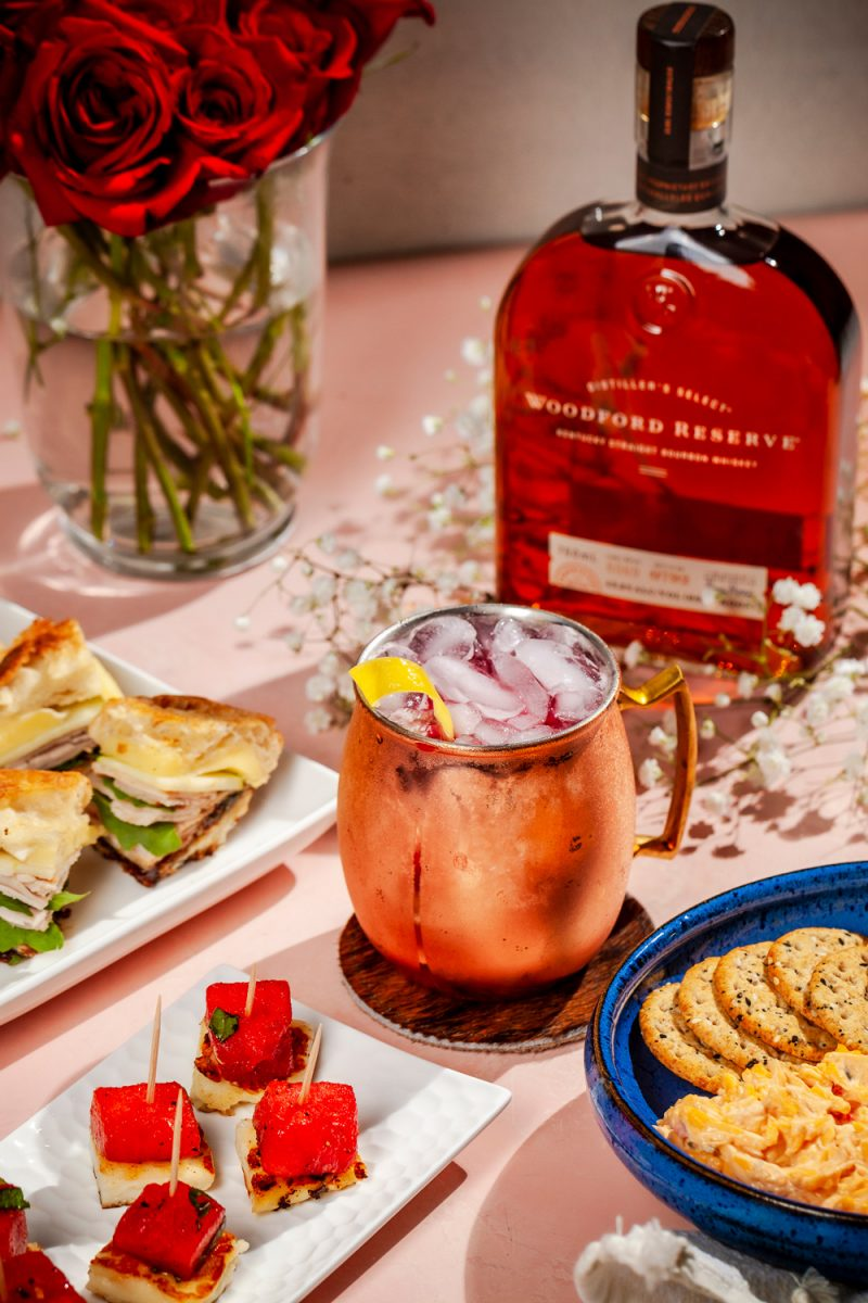 Kentucky Derby Party essentials featured by top US lifestyle blogger, Alicia Tenise - Woodford Spire |Kentucky Derby Party by popular D.C. lifestyle blogger, Alicia Tenise: image of a bottle of whiskey, vase of red roses, whiskey cocktail in a copper mug, crackers and pimento cheese, watermelon bites, and sandwiches with turkey and smoked brie.