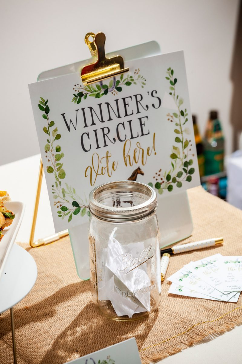 Kentucky Derby Party essentials featured by top US lifestyle blogger, Alicia Tenise |Kentucky Derby Party by popular D.C. lifestyle blogger, Alicia Tenise: image of a mason jar filled with folded pieces of paper next to a Winner's Circle paper on a white clipboard.