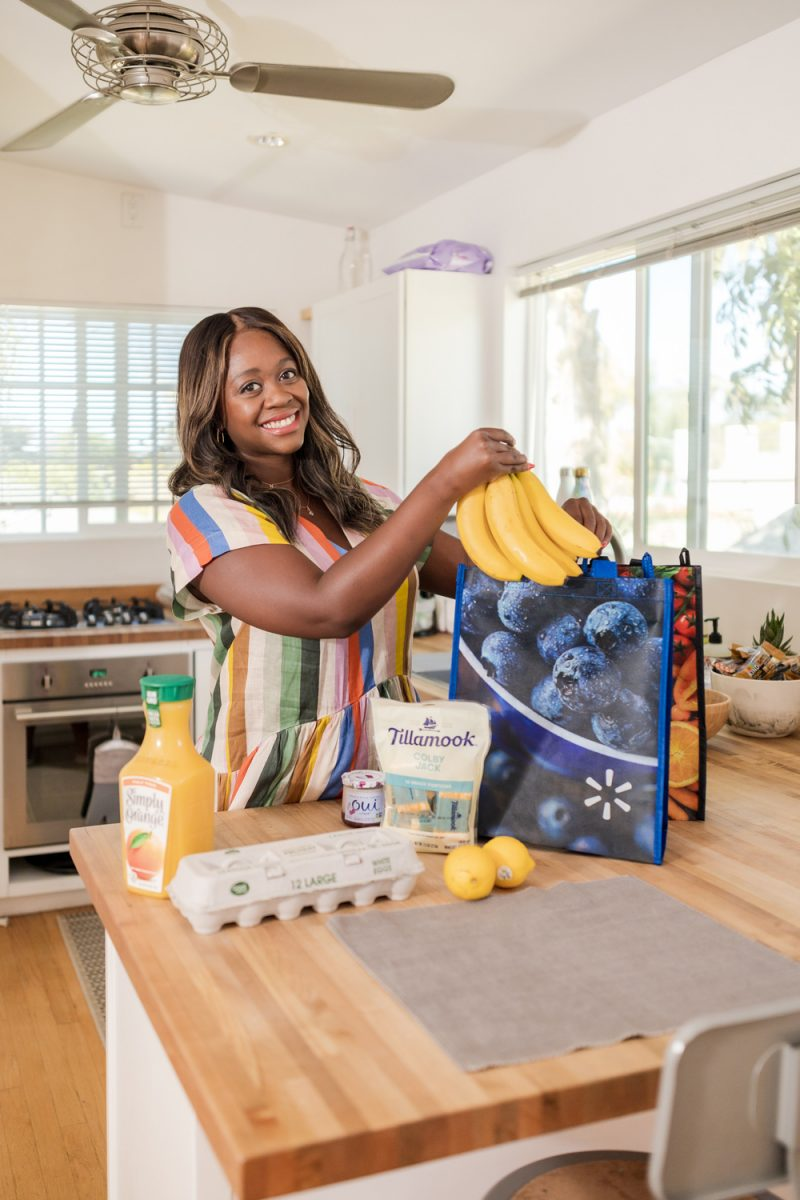 Walmart+ Grocery Pickup and Delivery | How to Eat Healthy on the Road by popular LA lifestyle blogger, Alicia Tenise: image of Alicia Tenise wearing a multi color stripe linen midi dress and pulling some bananas out of a re-usable Walmart shopping bag in her kitchen.