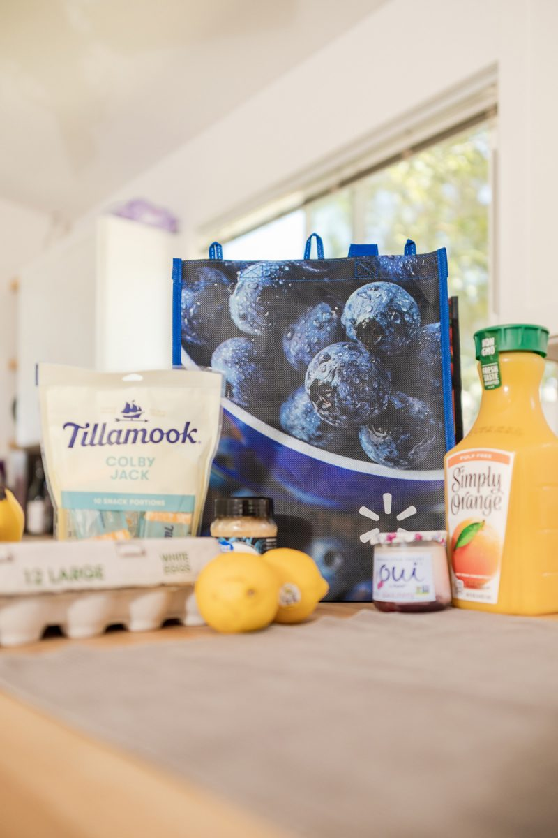 How to Eat Healthy on the Road by popular LA lifestyle blogger, Alicia Tenise: image of a re-usable Walmart shopping back behind a carton of eggs, Tillamook cheese squares, Oui yogurt, lemons, and Tampico simply orange orange juice.
