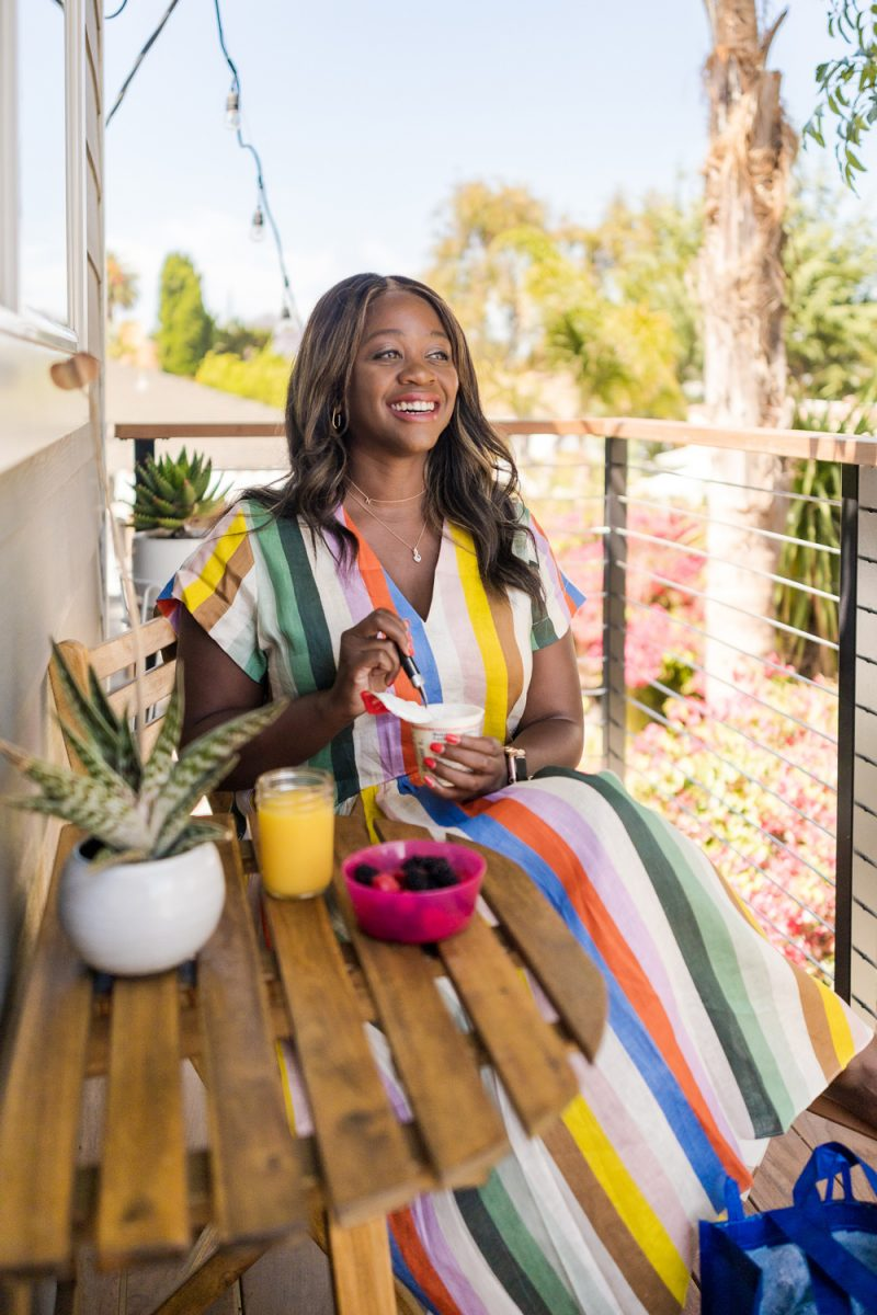 How to Eat Healthy on the Road by popular LA lifestyle blogger, Alicia Tenise: image of Alicia Tenise sitting outside next to a re-usable Walmart shopping bag and wearing a multi color stripe linen midi dress.