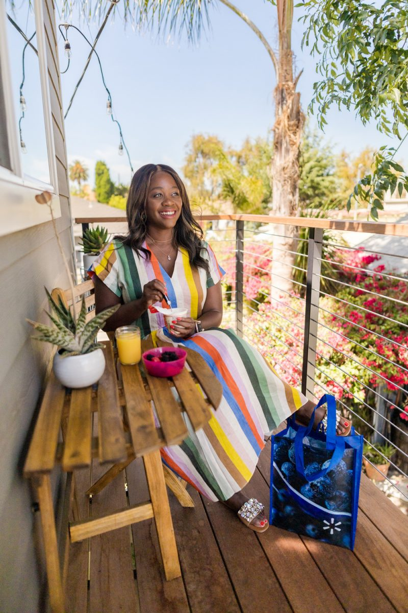WHIT TWO STRIPED LINEN MIDI DRESS | How to Eat Healthy on the Road by popular LA lifestyle blogger, Alicia Tenise: image of Alicia Tenise sitting outside next to a re-usable Walmart shopping bag and wearing a multi color stripe linen midi dress.