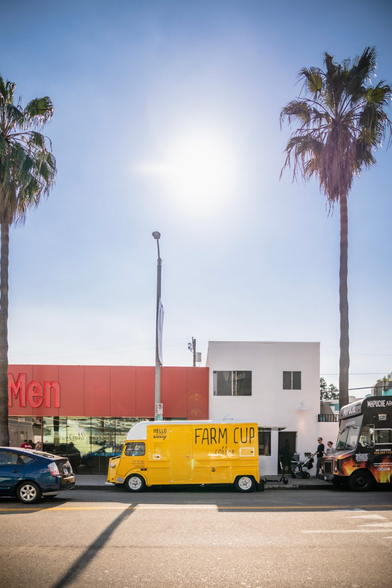 Juneteenth in Los Angeles: 5 Events to attend featured by top LA blogger, Alicia Tenise | Juneteenth Events by popular LA lifestyle blogger, Alicia Tenise: image of a yellow farm cup food truck parked under some palm trees in front of a white and red building.