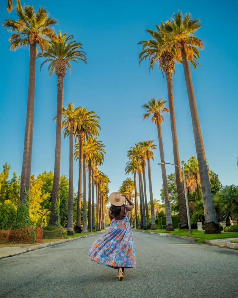 Beverly Hills, Free People Park Slope Maxi Dress | Moving Cross Country by popular LA lifestyle blogger, Alicia Tenise: image of Alicia Tenise wearing a floral print maxi dress, tan heel sandals, and straw hat and walking outside under some palm trees.