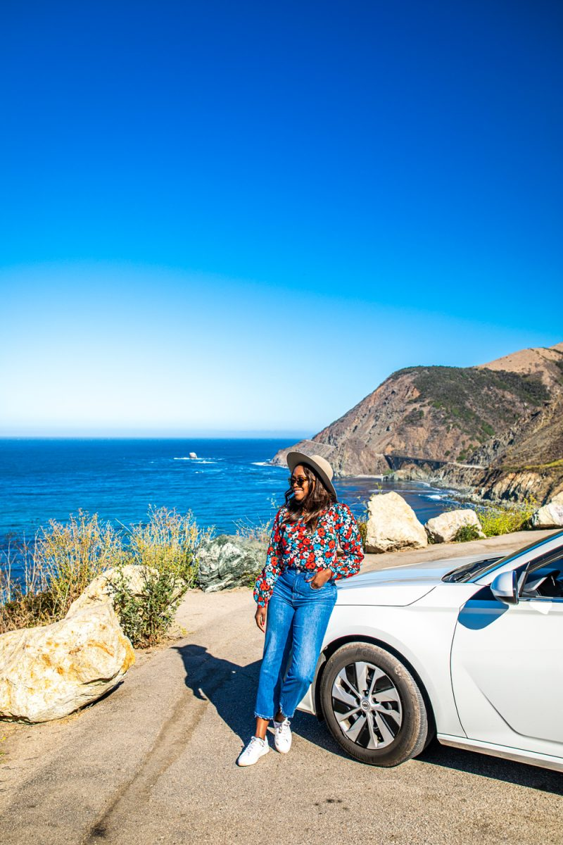 What to Wear on a Road Trip by popular LA fashion blogger, Alicia Tenise: image of Alicia Tenise wearing a floral print blouse, fedora hat, jeans, and white sneakers while leaning against a white car and looking out at the ocean.