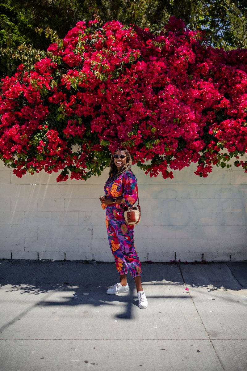 Farm Rio Macaw Twill Jumpsuits | Summer Jumpsuit by popular LA fashion blogger, Alicia Tenise: image of a woman wearing a summer jumpsuit with a pair of white sneakers and standing under a pink floral plant.