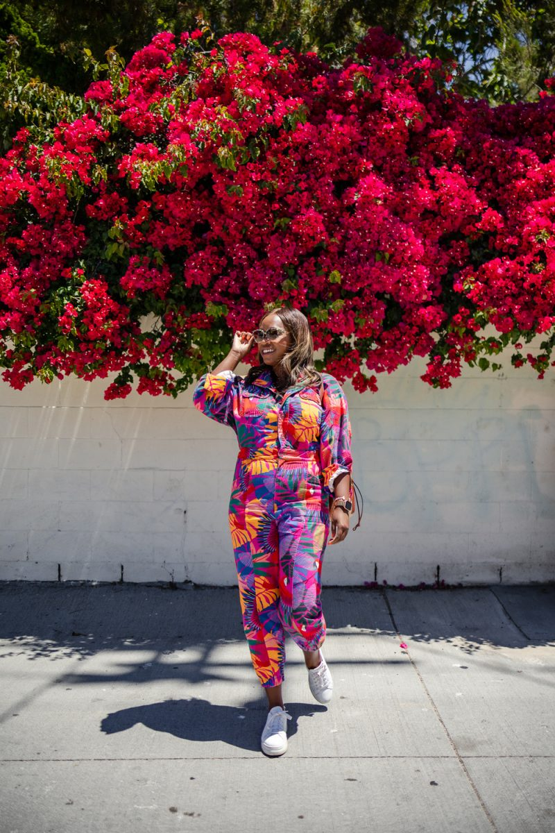 M.Gemi The Palestra Alta Platform Sneaker | Summer Jumpsuit by popular LA fashion blogger, Alicia Tenise: image of a woman wearing a summer jumpsuit with a pair of white sneakers and standing under a pink floral plant.
